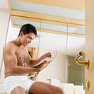 Side profile of a young man sitting in the bathroom and reading a magazine