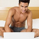 Portrait of a young man sitting on the bed with a laptop and smiling