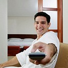 Portrait of a young man using a remote control and smiling