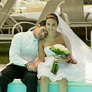 Portrait of a newlywed couple sitting at the poolside