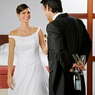 Groom looking at his bride and holding a bottle and glasses behind his back (thumbnail)