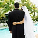 Rear view of a newlywed couple standing at the poolside