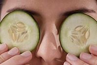 Close-up of a young woman covering her eyes with cucumber slices