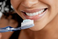 Close-up of a toothbrush with toothpaste in front of a young woman's mouth