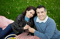 Portrait of a mid adult couple sitting on a picnic blanket and smiling