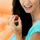 Close-up of a young woman holding a cherry tomato and smiling
