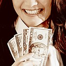 Close-up of a businesswoman holding dollar bills and smiling
