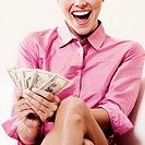 Close-up of a businesswoman holding dollar bills and laughing