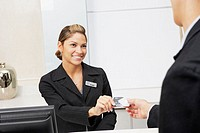 Customer giving a credit card to a female receptionist