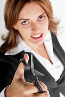 Portrait of a businesswoman holding a pair of scissors and clenching her teeth