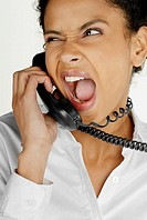 Close-up of a businesswoman talking on telephone and making a face