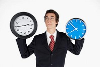 Close-up of a businessman holding clocks