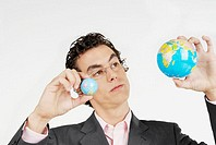 Close-up of a businessman holding two globes