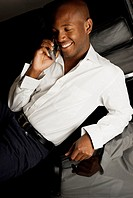 High angle view of a young man using a mobile phone and smiling
