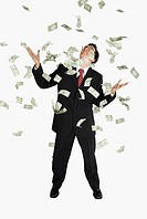 American dollar bills raining down on a businessman
