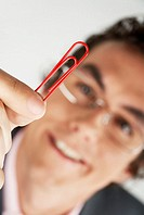 Young man holding a paper clip
