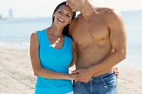 Close-up of a young couple standing on the beach (thumbnail)