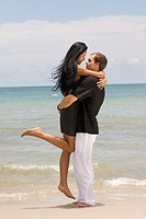 Side profile of a young couple embracing each other on the beach