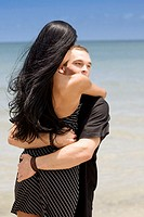Close-up of a young couple embracing each other on the beach
