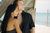 Close-up of a young couple standing on the beach and looking away