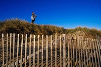 Low angle view of a woman standing on top of a hill, Cape Cod, Massachusetts, USA