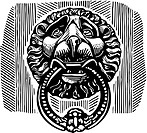 A bnlack and white door knocker in the shape of a lion holding a ring in its mouth