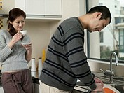 Young couple in kitchen, woman watching man washing dishes