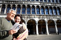 Italy, Venice, Piazza San Marco, mature couple looking at travel guide