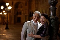 Italy, Venice, couple standing by lamp post at night, portrait