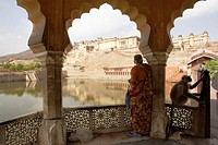 India, Rajasthan, woman standing on veranda, Amber Fort in distance