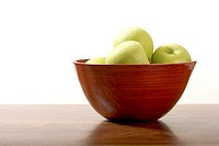 Green apples in polished brown wood bowl