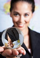 Businesswoman holding crystal ball, smiling, portrait