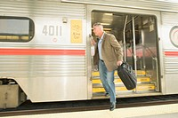 Businessman stepping off train