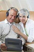 Mature man and woman watching movie on laptop aboard airplane