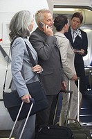 People boarding airplane (focus on senior man talking on cell phone)