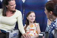 Flight attendant talking to woman with daughter (6-8) on airplane