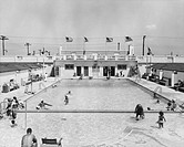 People relaxing in outdoor pool (B&W), elevated view