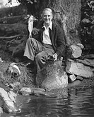 Senior man sitting by water, holding up fish (B&W), portrait