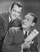 Two men in studio, one holding insurance policy (B&W)