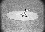 Baseball pitcher throwing ball, (B&W), elevated view