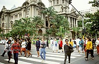 People crossing West Street, the main thoroughfare of Durban, South Africa. The large building in the background is City Hall.