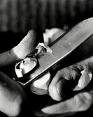 Close-up view of the hands of a person cutting an object with knife