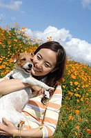 Smiling Asian woman holding dog in field of flowers