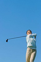 Young Asian woman swinging a golf club