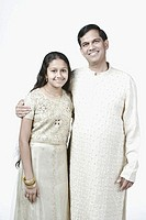 Portrait of a mature man standing with his arm around his daughter