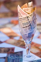 Close-up of Indian banknotes in a stem glass