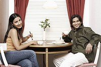 Portrait of a young couple eating in a restaurant