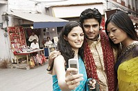 Close-up of a young man and two young women taking a photograph of themselves