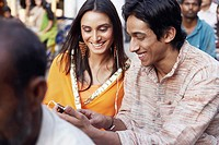 Close-up of a young couple sitting on a rickshaw listening to an MP3 player