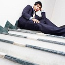 Low angle view of a businessman sitting on the staircase